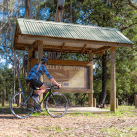 A cyclist at the old Shelley Station sign on the High Country Rail Trail